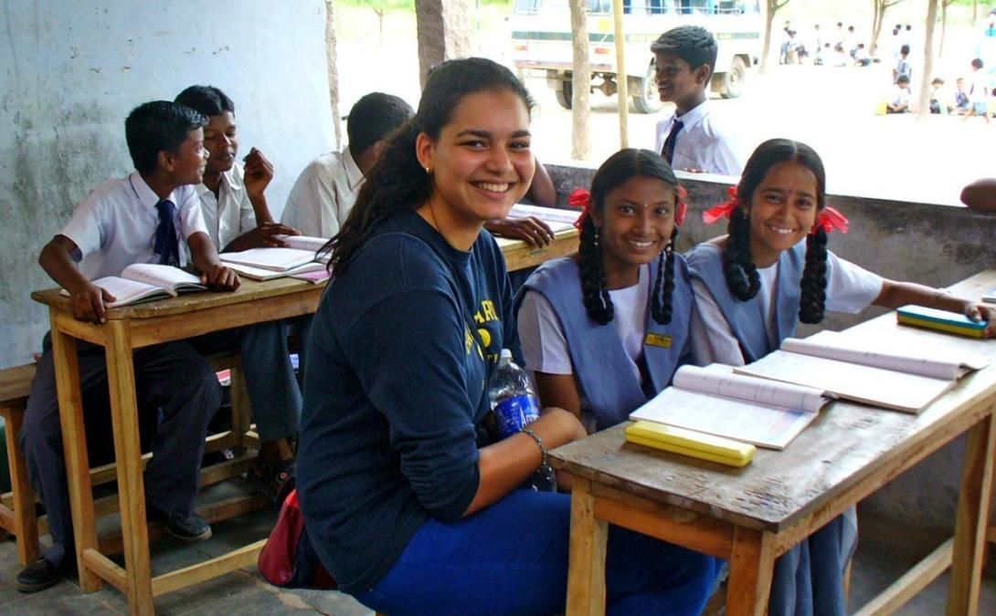 Teaching volunteer helps her students with an English reading exercise during class in India.
